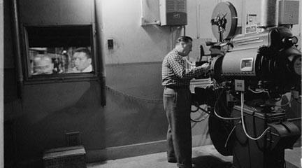 film negative, Man working with a projector in a movie theater, 1958 Feb. 9, Mar